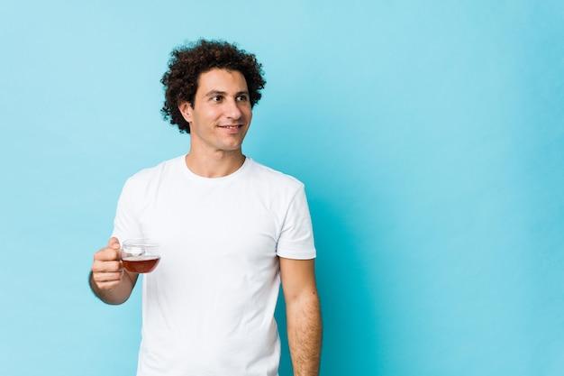 Młody caucasian kędzierzawy mężczyzna trzyma herbacianą filiżankę ono uśmiecha się ufny z krzyżować rękami.