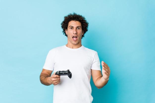 Młody caucasian kędzierzawy mężczyzna trzyma kontrolera gier świętuje zwycięstwo lub sukces