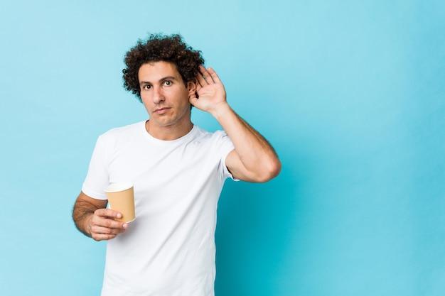 Młody caucasian kędzierzawy mężczyzna trzyma na wynos kawę próbuje słuchać plotki.