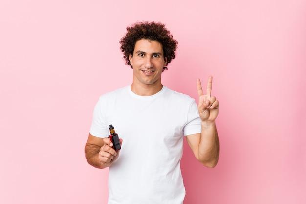 Młody caucasian kędzierzawy mężczyzna trzyma vape pokazuje numer dwa z palcami.