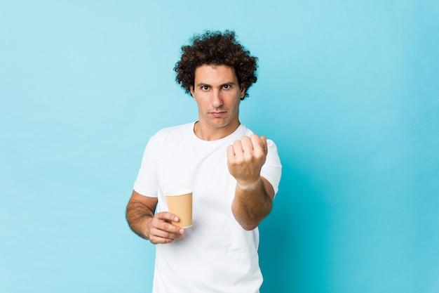 Młody caucasian kędzierzawy mężczyzna trzyma wynos kawę pokazuje pięść kamera, agresywny wyraz twarzy.