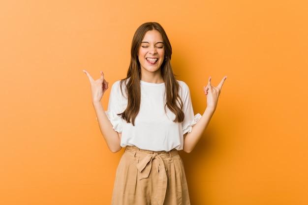 Młody caucasian kobieta pokazuje rockowego gest z palcami