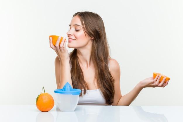 Młody caucasian kobiety mienie robi sokowi pomarańczowemu