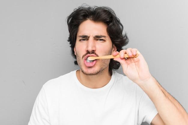 Młody caucasian mężczyzna czyści jego zęby szczoteczką do zębów odizolowywającymi w szarej ścianie