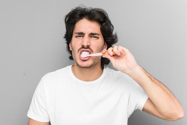 Młody caucasian mężczyzna czyści zęby z toothbrush odizolowywającym w szarej ścianie