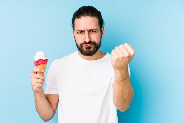Młody caucasian mężczyzna je lody odizolowywał pokazywać pięść, agresywny wyraz twarzy.
