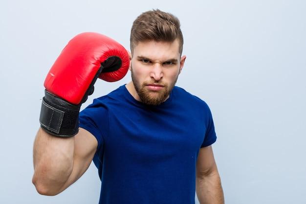 Młody caucasian mężczyzna jest ubranym bokserskie rękawiczki