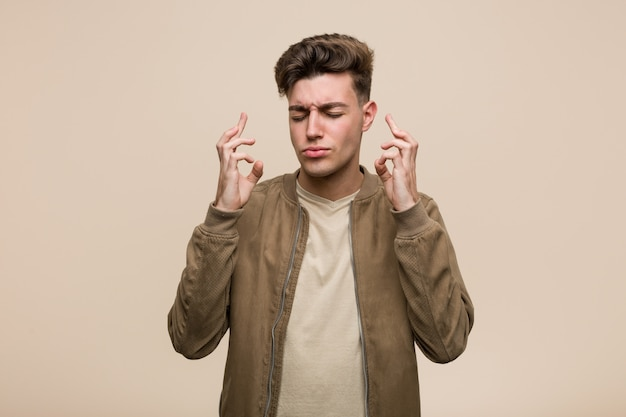 Młody caucasian mężczyzna jest ubranym brown kurtkę krzyżuje palce dla mieć szczęście