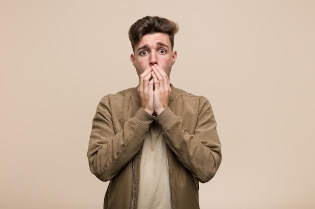 Młody caucasian mężczyzna jest ubranym brown kurtkę okaleczającą i przestraszoną.
