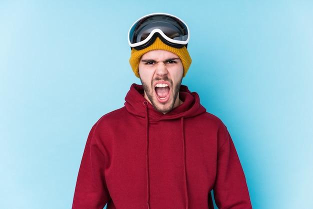 Młody caucasian mężczyzna jest ubranym narciarskiego ubrania odizolowywał krzyczeć bardzo gniewny i agresywny.