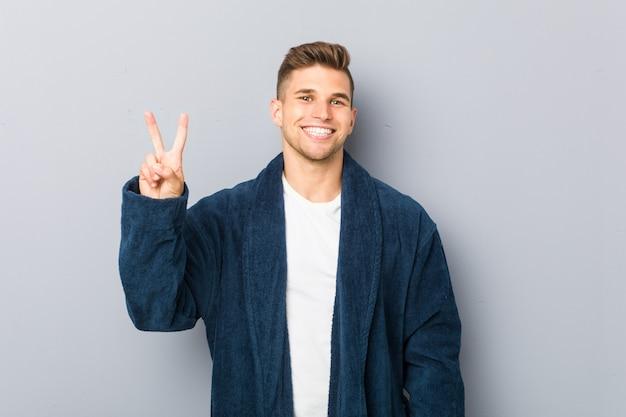 Młody caucasian mężczyzna jest ubranym piżamę pokazuje zwycięstwo znaka i uśmiecha się szeroko.