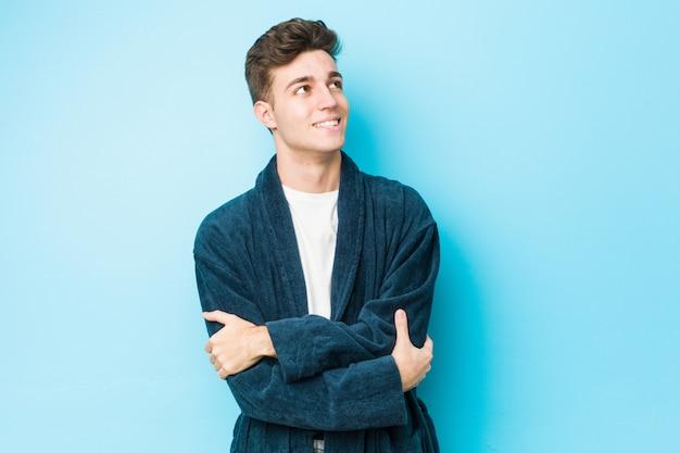 Młody caucasian mężczyzna jest ubranym piżamy ono uśmiecha się ufny z krzyżować rękami.