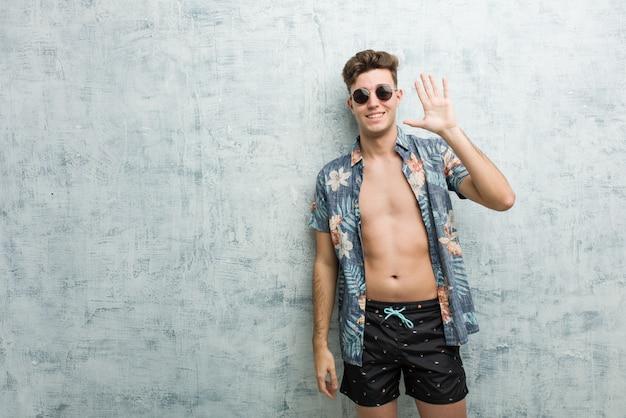 Młody caucasian mężczyzna jest ubranym swimsuit ono uśmiecha się rozochoconego seans liczba pięć z palcami.