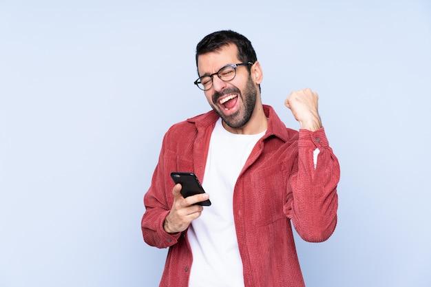 Młody caucasian mężczyzna jest ubranym sztruksową kurtkę nad błękitnym wallwith telefonem w zwycięstwo pozyci