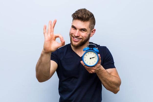 Młody caucasian mężczyzna mienia budzik rozochocony i ufny pokazuje ok gest.