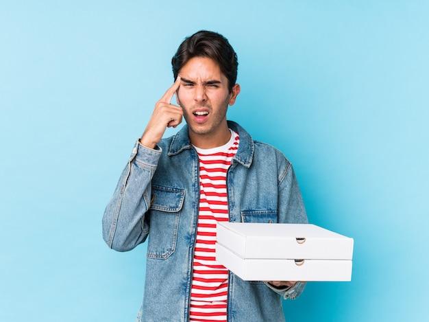 Młody caucasian mężczyzna mienia pizze odizolowywać pokazywać rozczarowanie gest z palcem wskazującym.