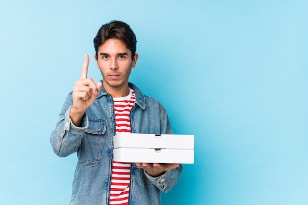 Młody caucasian mężczyzna mienia pizze odizolowywał pokazywać liczbę jeden z palcem.