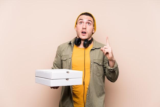 Młody caucasian mężczyzna mienia pizzy wskazuje do góry z rozpieczętowanym usta.