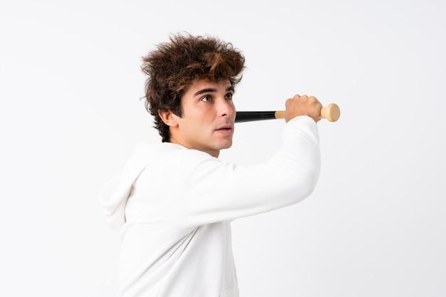 Młody caucasian mężczyzna nad odosobnioną biel ścianą bawić się baseballa