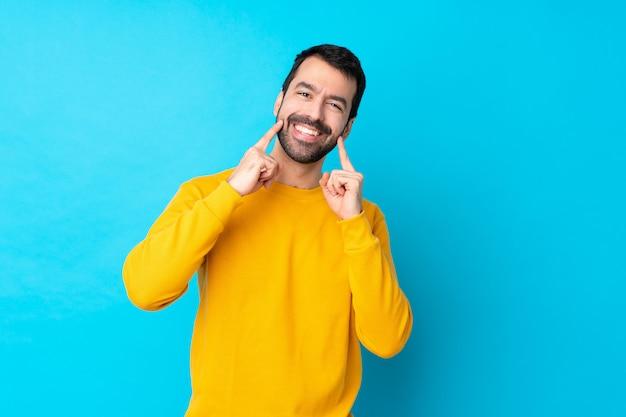 Młody caucasian mężczyzna nad odosobnioną błękit ścianą ono uśmiecha się z szczęśliwym i przyjemnym wyrażeniem