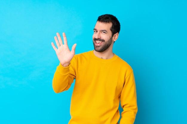 Młody caucasian mężczyzna nad odosobnioną błękit ścianą salutuje z ręką z szczęśliwym wyrażeniem