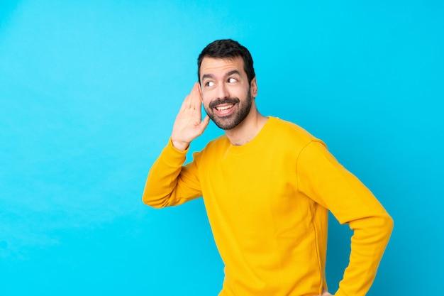 Młody caucasian mężczyzna nad odosobnioną błękit ścianą słucha coś stawiając rękę na ucho