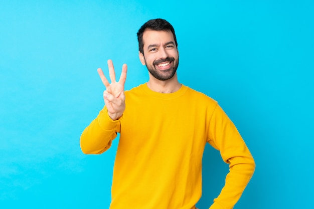 Młody caucasian mężczyzna nad odosobnioną błękit ścianą szczęśliwą i liczy trzy z palcami