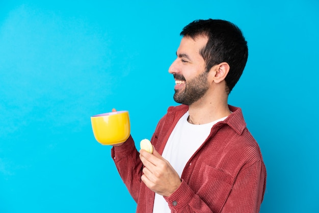 Młody caucasian mężczyzna nad odosobnioną błękit ścianą trzyma kolorowych francuskich macarons i filiżankę mleka