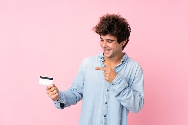 Młody caucasian mężczyzna nad odosobnioną menchii ścianą trzyma kartę kredytową