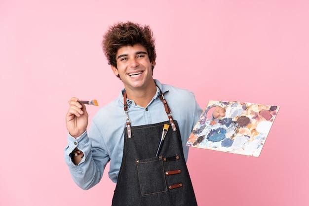 Młody caucasian mężczyzna nad odosobnioną menchii ścianą trzyma paletę