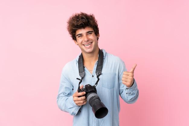 Młody caucasian mężczyzna nad odosobnioną menchii ścianą z profesjonalistą kamerą z kciukiem up i