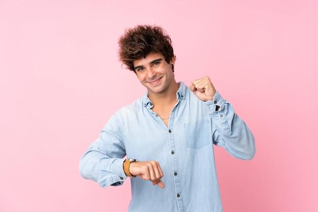 Młody caucasian mężczyzna nad odosobnioną menchii ścianą z wristwatch i szczęśliwym wyrażeniem
