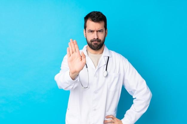 Młody caucasian mężczyzna nad odosobnioną ścianą jest ubranym doktorską togę i robi przerwie podpisywać