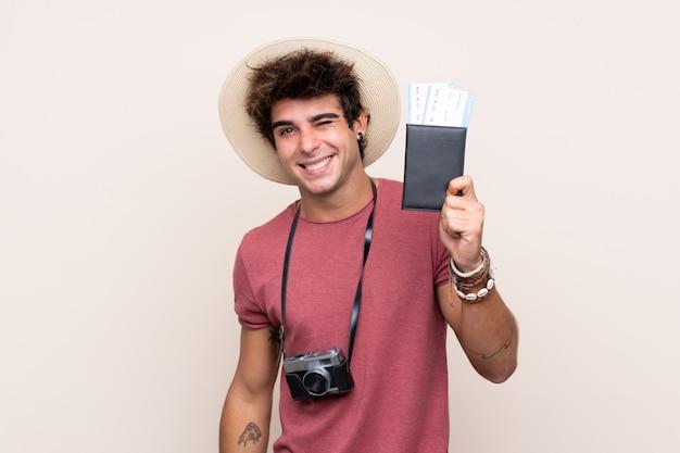 Młody caucasian mężczyzna nad odosobnioną ścianą w wakacje trzyma paszport i samolot z kciukiem up