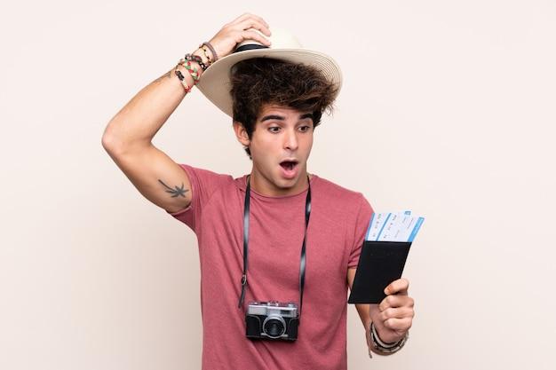 Młody caucasian mężczyzna nad odosobnioną ścianą w wakacje z samolotowymi biletami i zaskakujący