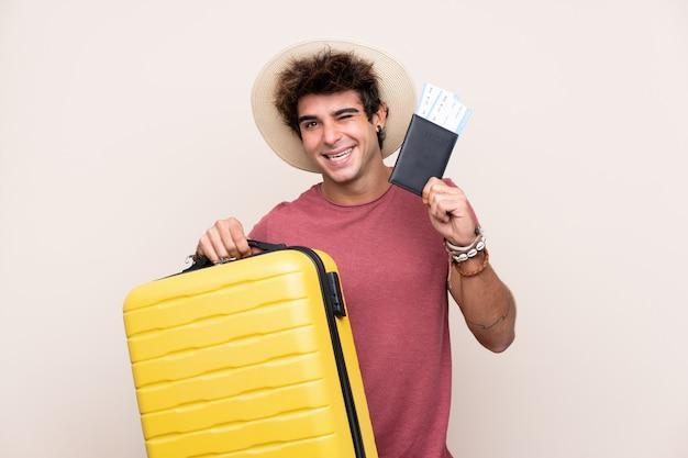 Młody caucasian mężczyzna nad odosobnioną ścianą w wakacje z walizką i paszportem