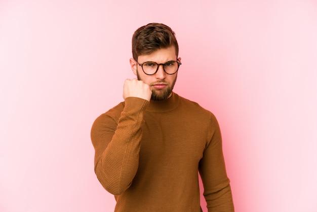 Młody caucasian mężczyzna odizolowywający na menchii pokazuje pięść, agresywny wyraz twarzy.