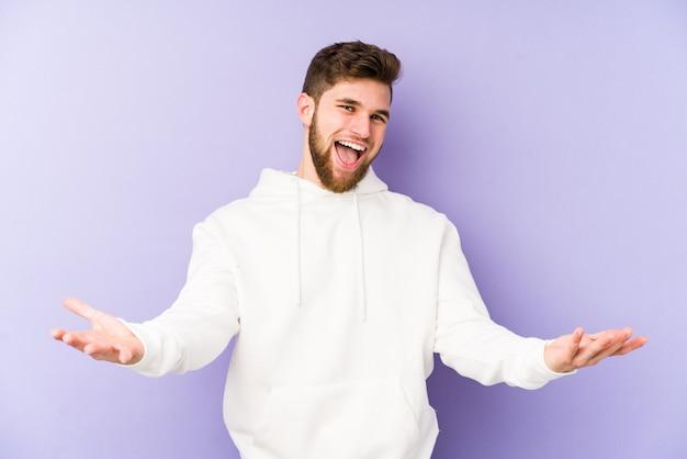 Młody caucasian mężczyzna odizolowywający na purpurach pokazuje mile widziany wyrażenie.