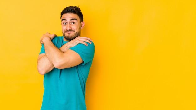 Młody caucasian mężczyzna odizolowywający na żółtych uściskach, ono uśmiecha się beztroski i szczęśliwy.