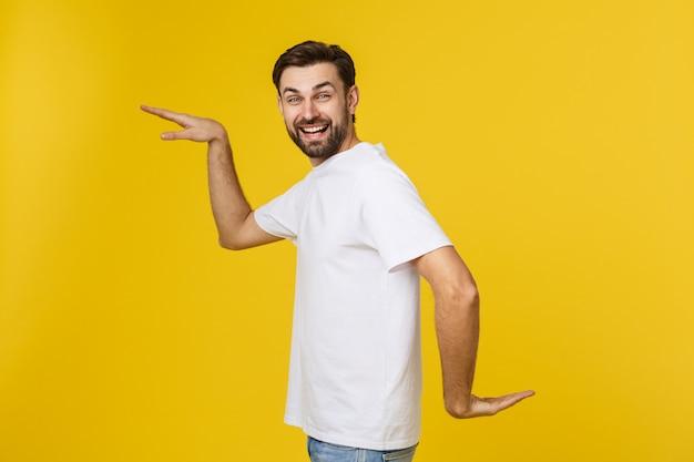 Młody caucasian mężczyzna odizolowywający na żółtym tanu i zabawie