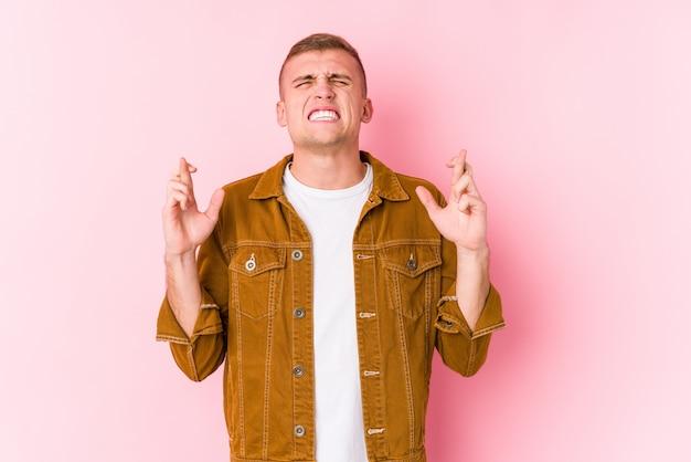 Młody caucasian mężczyzna odizolowywał skrzyżowanie palców dla mieć szczęście