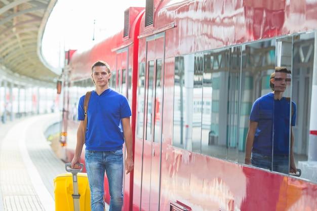 Młody caucasian mężczyzna podróżuje pociągiem z bagażem przy stacją