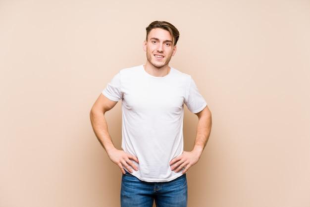 Młody caucasian mężczyzna pozować odizolowywam szczęśliwy, uśmiechnięty i rozochocony.