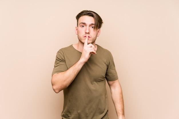 Młody caucasian mężczyzna pozować odizolowywam utrzymujący sekret lub pytać o ciszę.