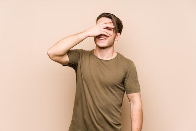 Młody caucasian mężczyzna pozuje odosobnionego mrugnięcie przy palcami, zawstydzona nakrycie twarz.