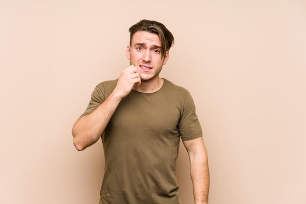 Młody caucasian mężczyzna pozuje odosobnionych zjadliwych paznokcie, nerwowych i bardzo niespokojnych.