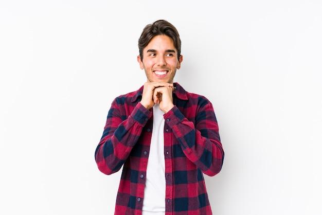 Młody caucasian mężczyzna pozuje w różowej ścianie odizolowywającej utrzymuje ręki pod podbródkiem, patrzeje szczęśliwie na boku.