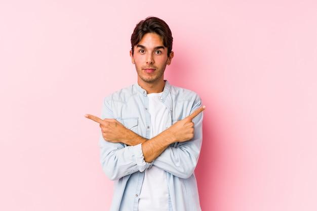Młody caucasian mężczyzna pozuje w różowej ścianie odizolowywającej wskazuje na boki, próbuje wybierać między dwiema opcjami.