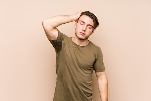 Młody caucasian mężczyzna pozuje zmęczonego i bardzo śpiącego utrzymuje rękę na głowie.