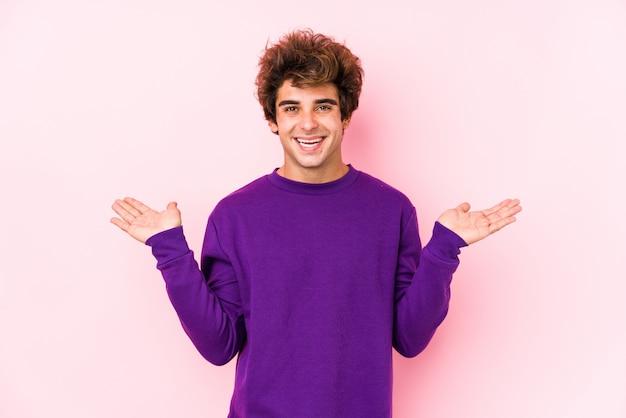 Młody caucasian mężczyzna przeciw różowej ścianie odizolowywającej robi skala z rękami, czuje się szczęśliwy i pewny siebie.